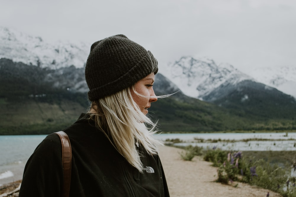 woman in black knit cap and black jacket