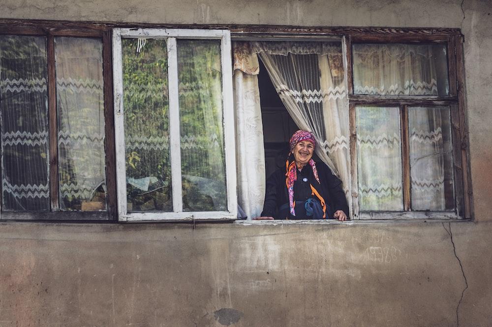 woman in black jacket standing near white wooden framed glass window