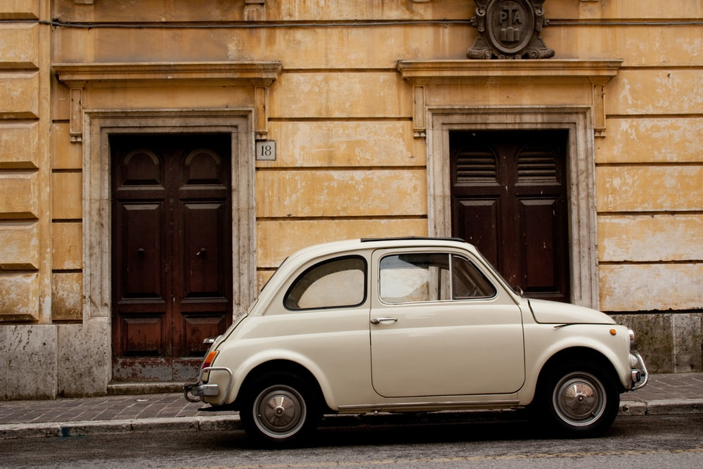 white volkswagen beetle parked beside brown brick building during daytime