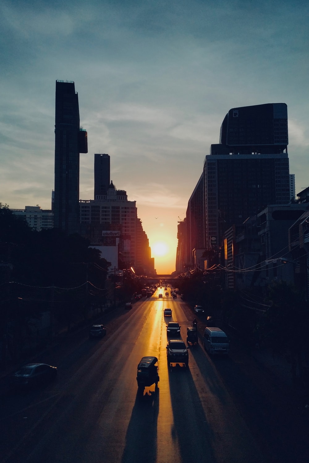 cars on road between high rise buildings during sunset
