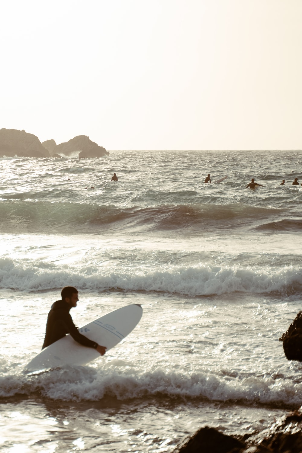 man in white surfboard surfing on sea waves during daytime