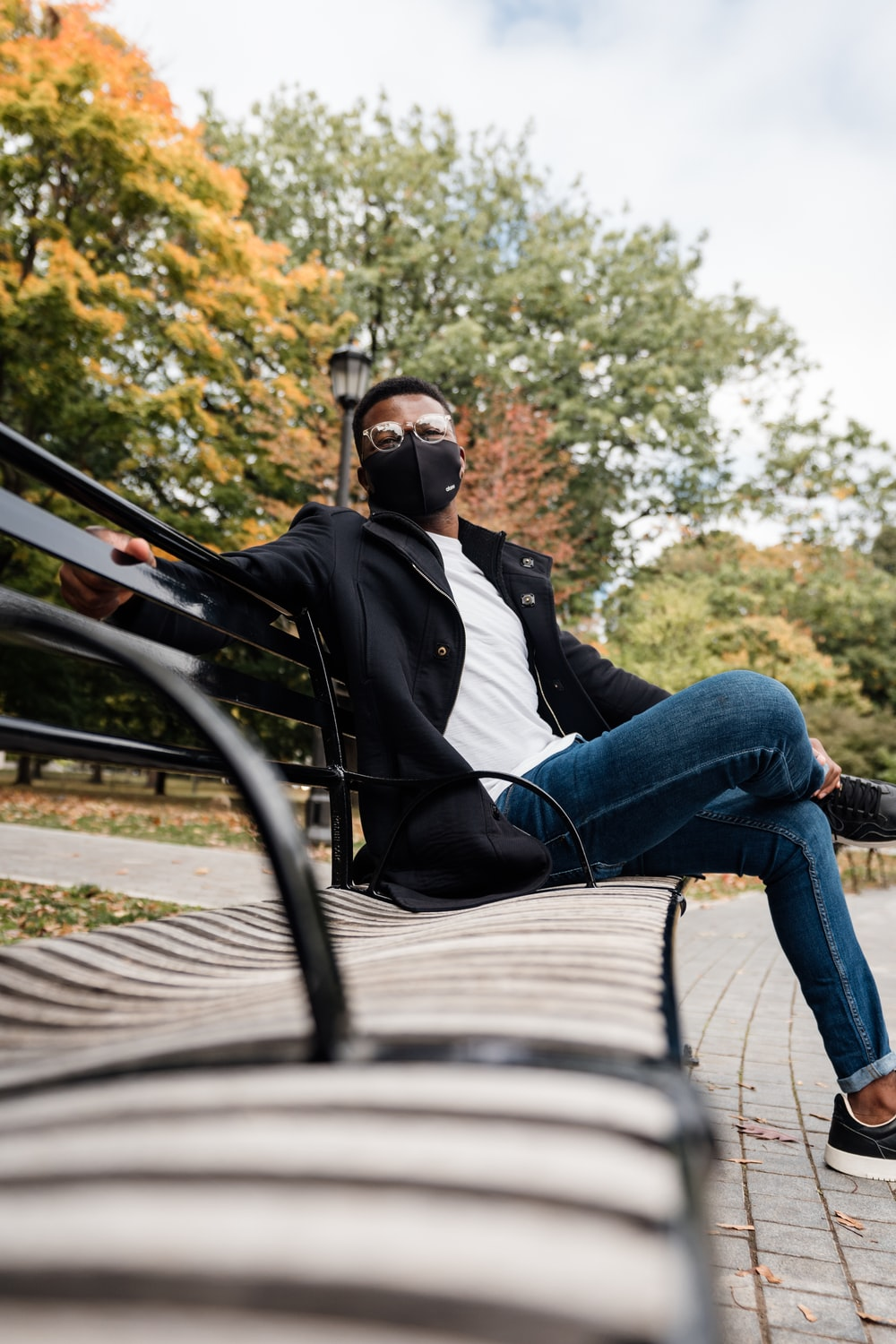 man in black jacket and blue denim jeans sitting on black metal bench during daytime