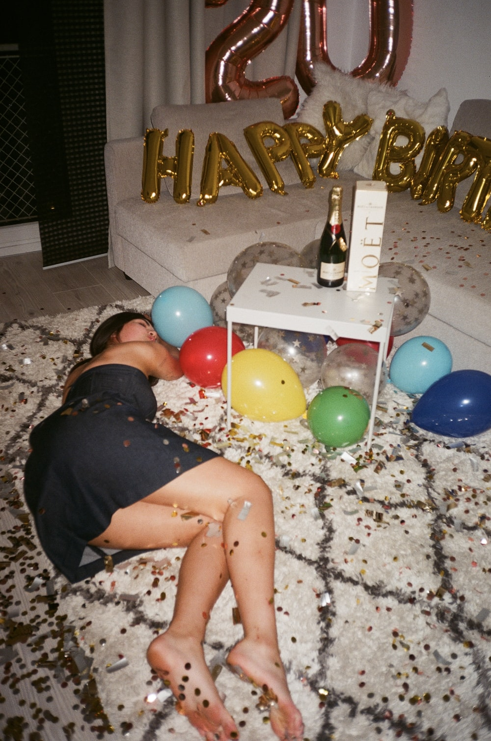 woman in black shirt lying on floor with balloons
