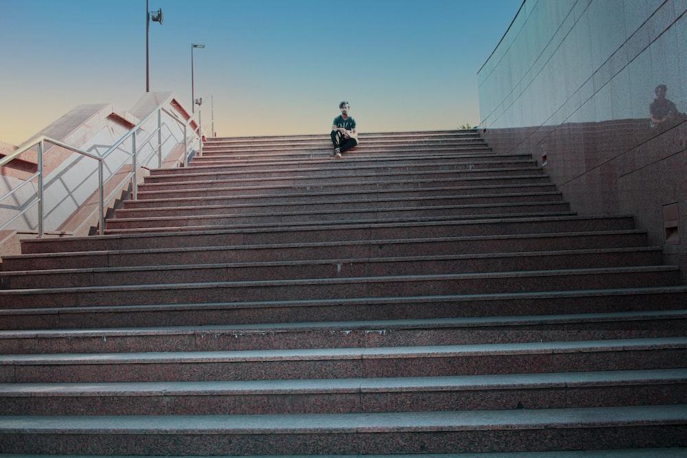 man in black jacket riding bicycle on brown concrete stairs during daytime