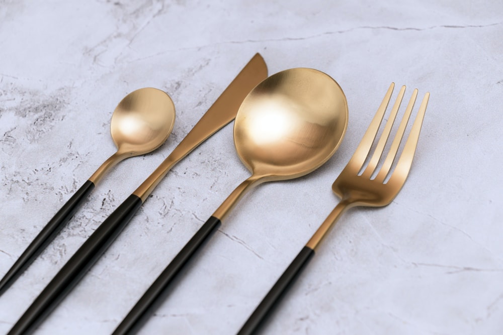 silver spoon and fork on white textile