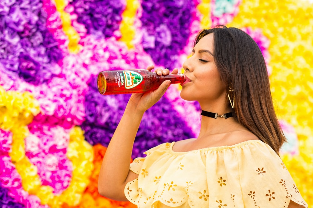 woman in white floral dress drinking coca cola