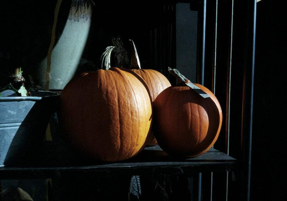 orange pumpkin on black wooden table