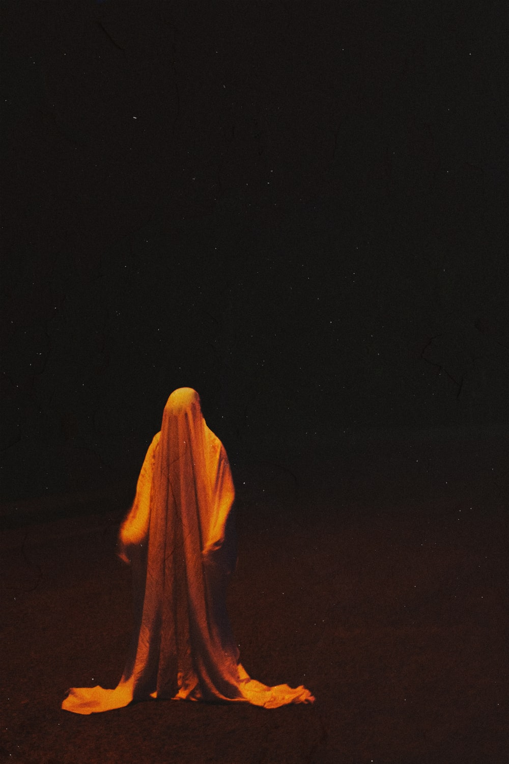person in yellow hijab standing on brown field during night time