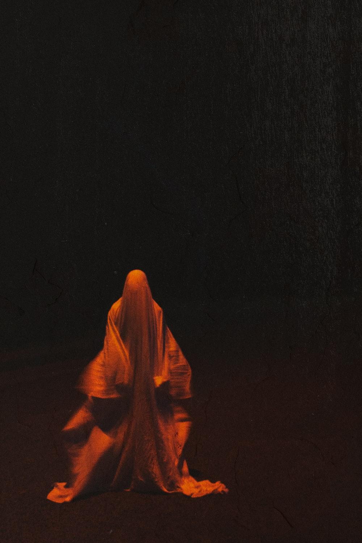 woman in orange hijab standing on black surface