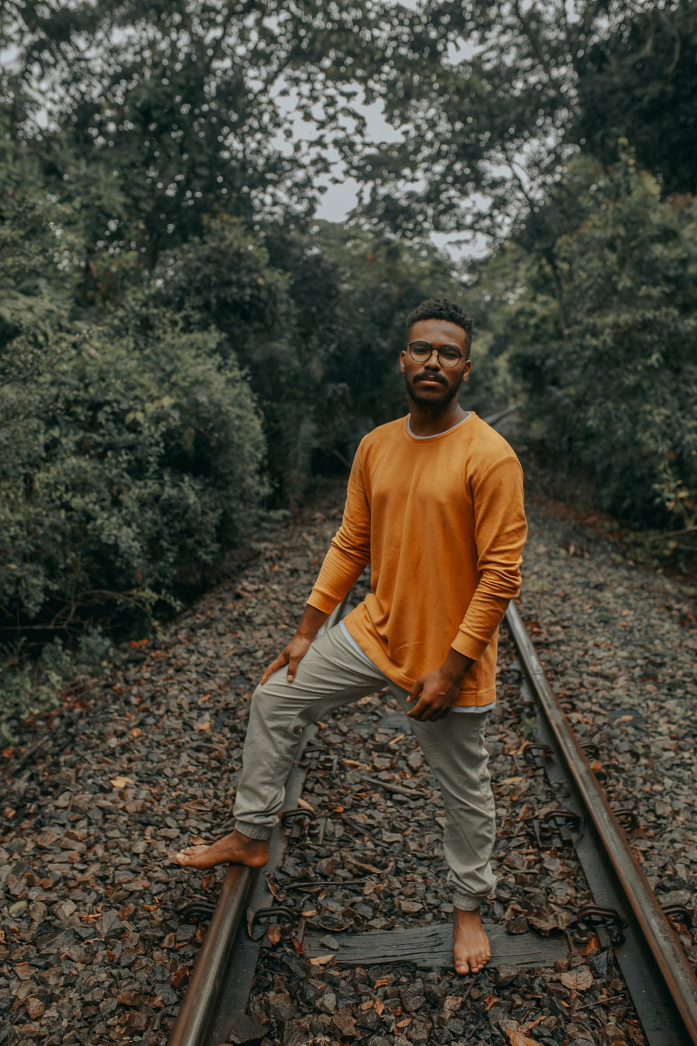 man in brown sweater and beige pants standing on train rail during daytime