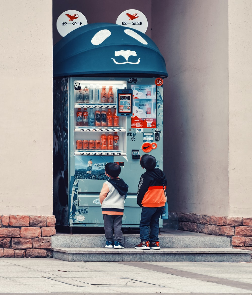 man in black and red jacket standing beside pepsi vending machine