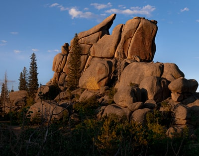 brown rock formation near green trees under blue sky during daytime wyoming teams background