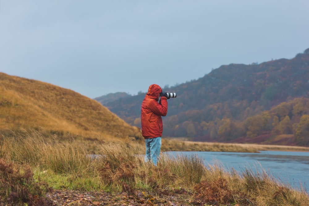 man in red jacket standing on grass field near body of water during daytime