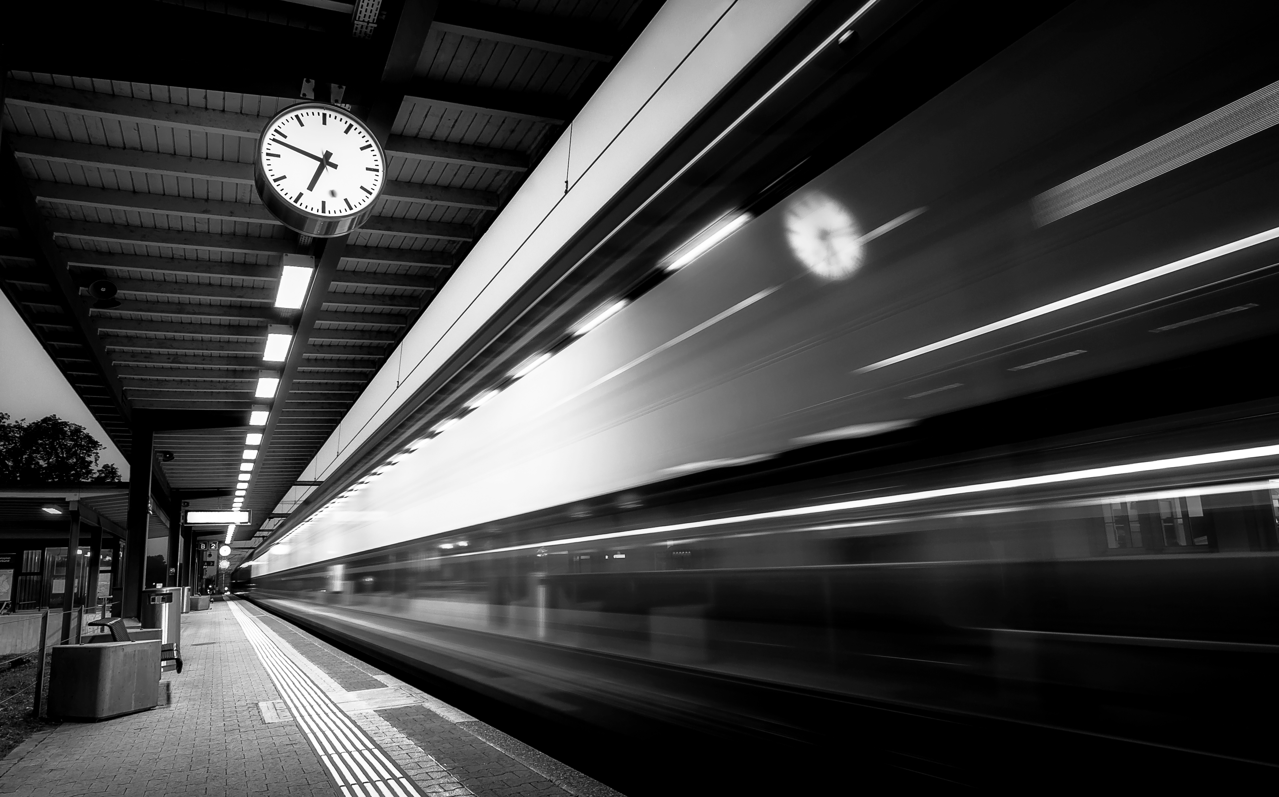 Train departing from the station in black and white