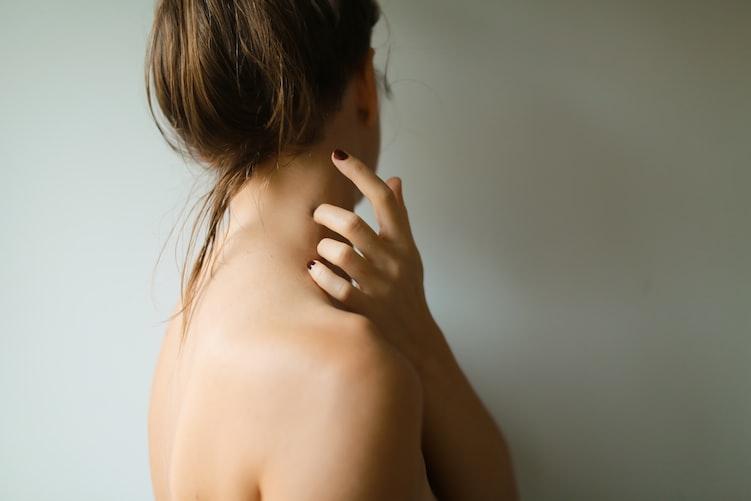 ragazza con i capelli legati alti e spalle nude che si gratta il collo