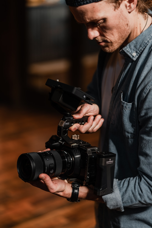 man in gray suit holding black dslr camera