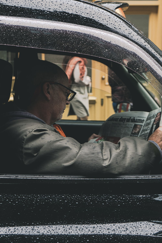 man in gray jacket driving car