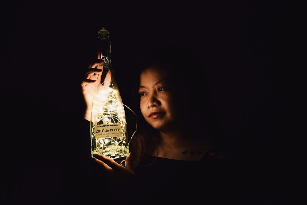 woman in black shirt holding clear glass bottle