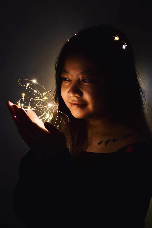 woman holding string lights in dark room