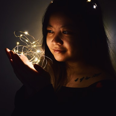 woman holding string lights in dark room