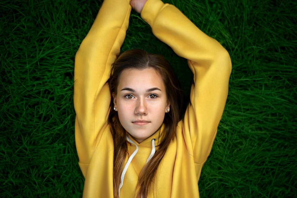 woman in yellow long sleeve shirt lying on green grass