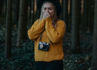 woman in brown knit sweater and black hat standing in forest during daytime