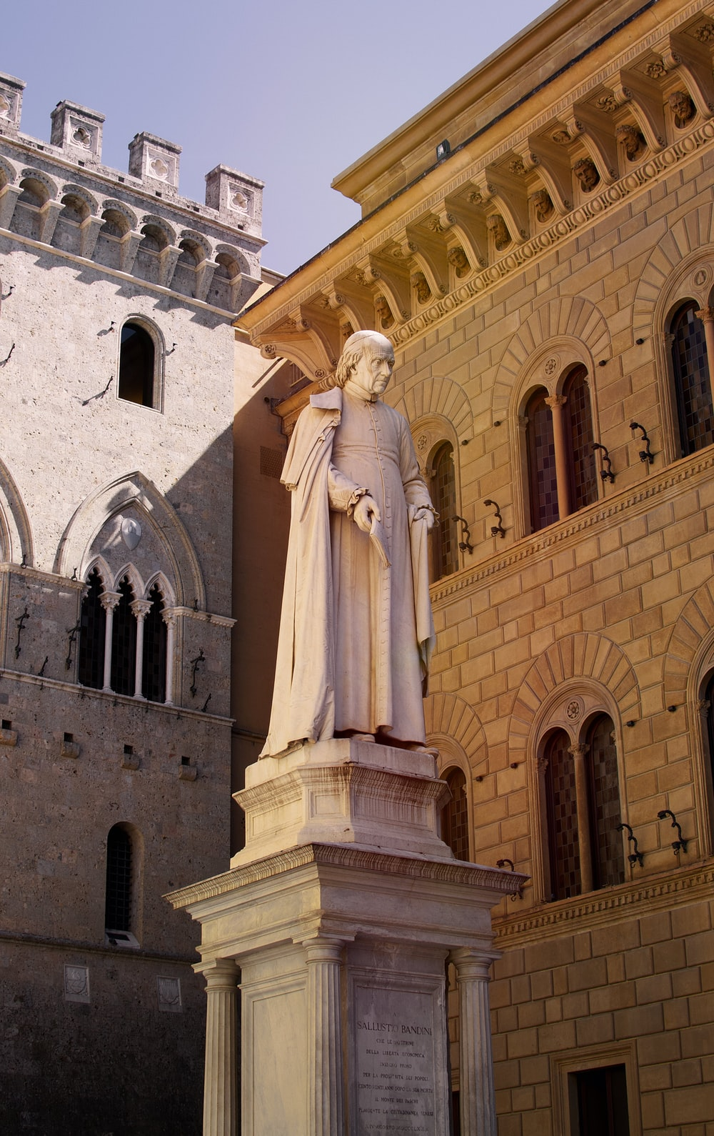 white statue of a woman in front of a building