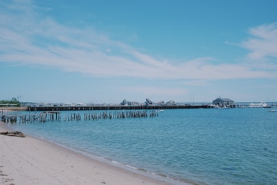 white wooden dock on sea under blue sky during daytime cape cod teams background