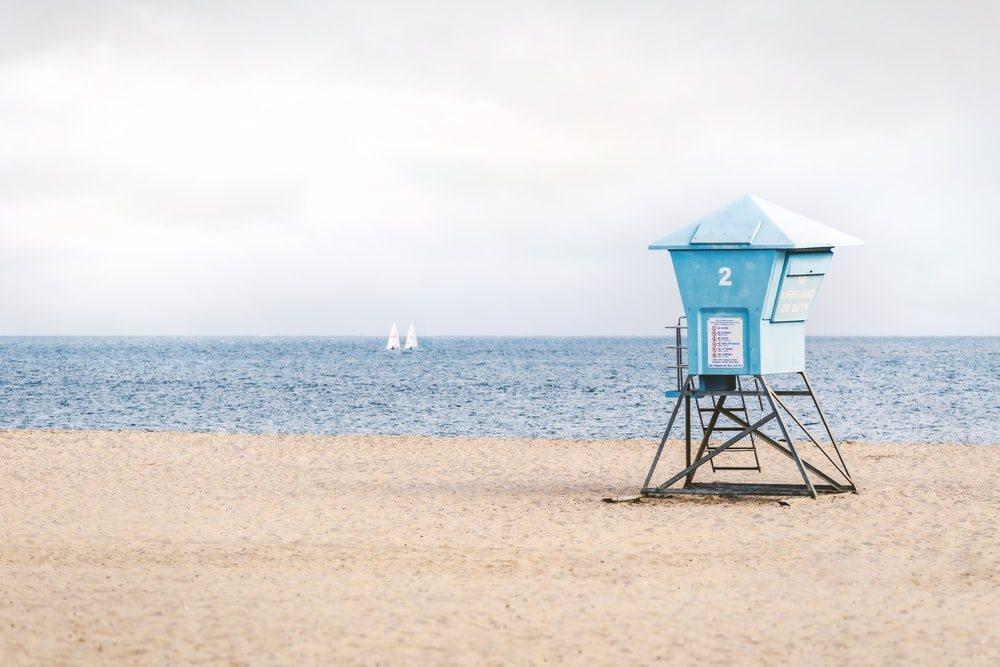 blue lifeguard house on beach during daytime
