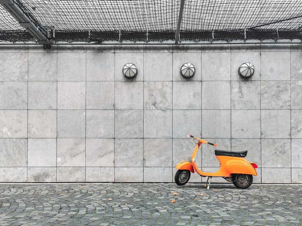 orange and black motor scooter parked beside gray concrete wall