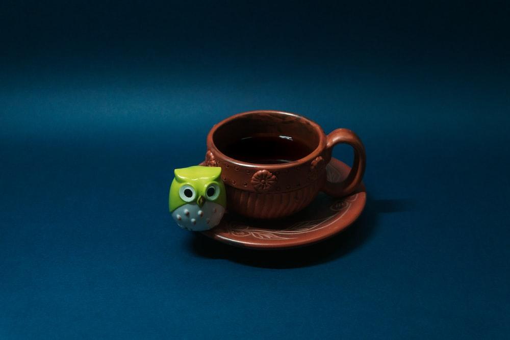 green and brown ceramic mug on saucer