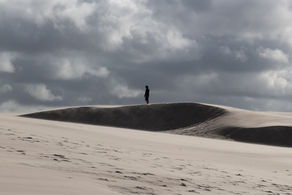 person walking on white sand under white clouds during daytime