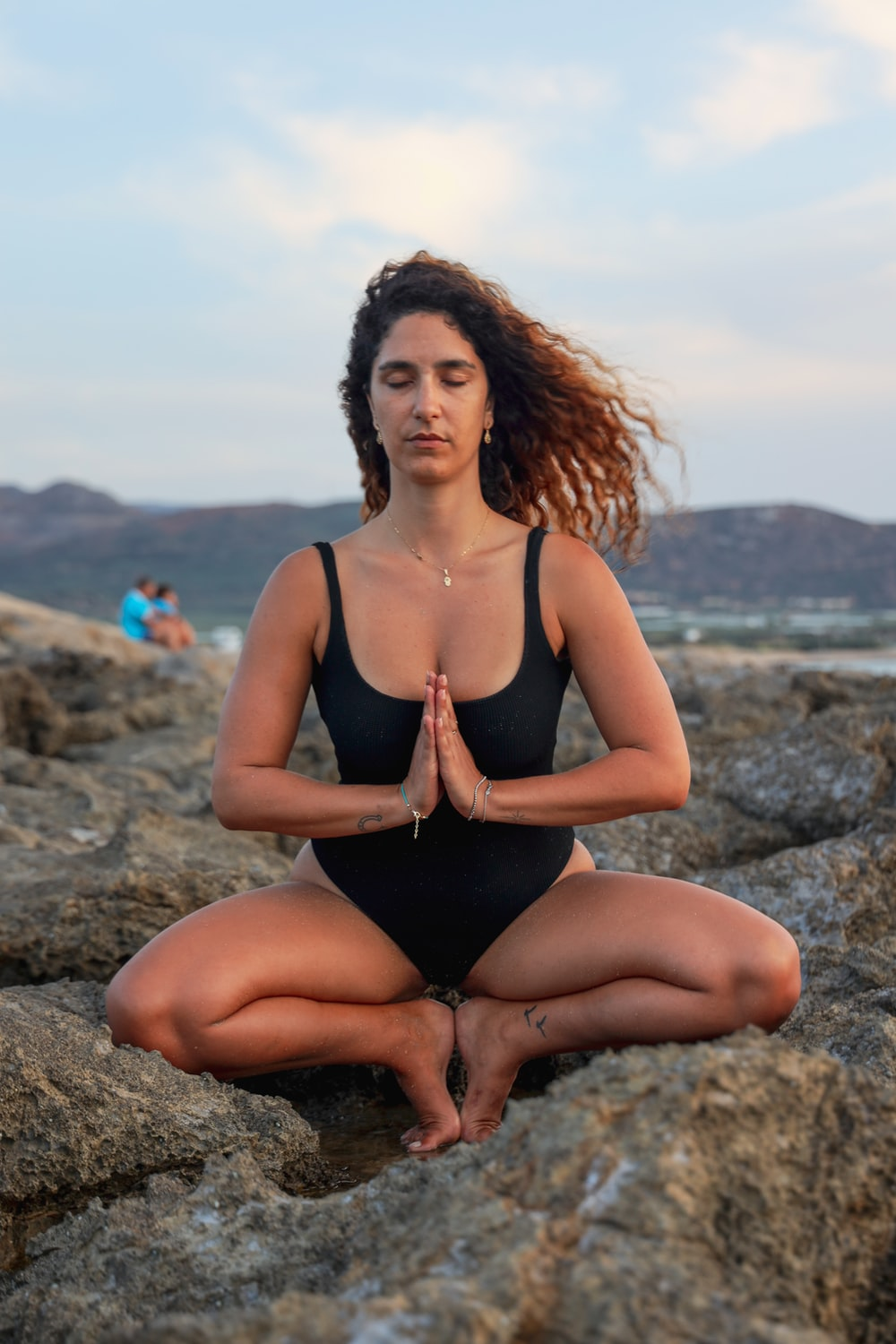 woman in black tank top sitting on gray rock during daytime