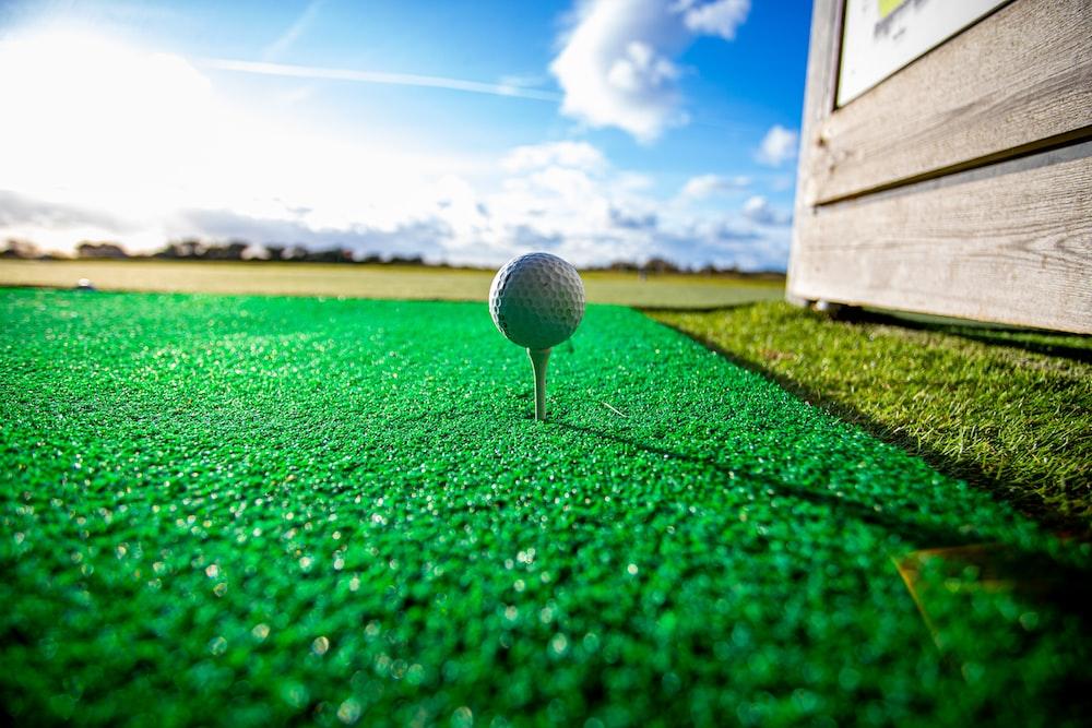 white golf ball on green grass field under blue sky during daytime