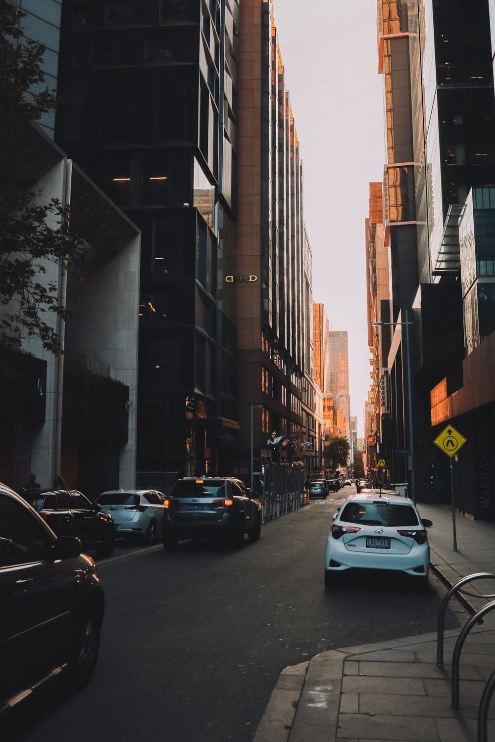 cars parked on side of the road in between high rise buildings during daytime