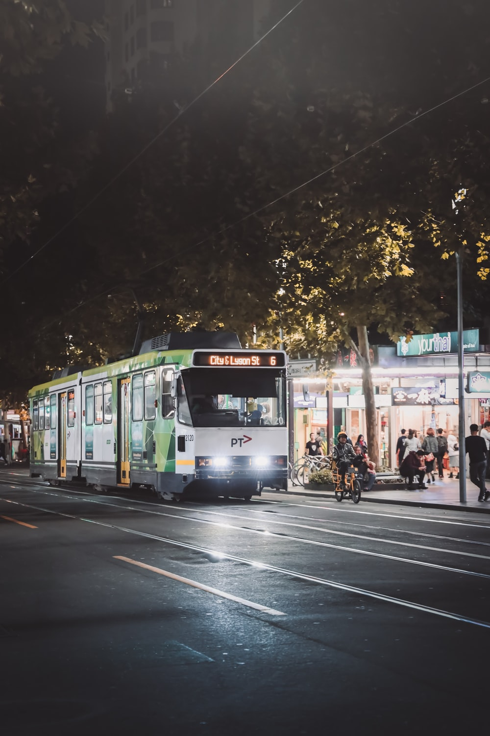 people walking on street near green and white tram during night time