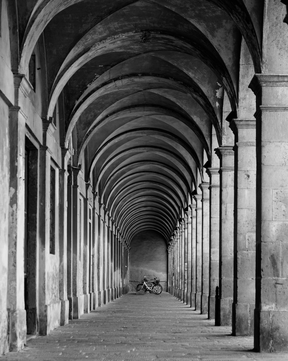 grayscale photo of person walking on hallway
