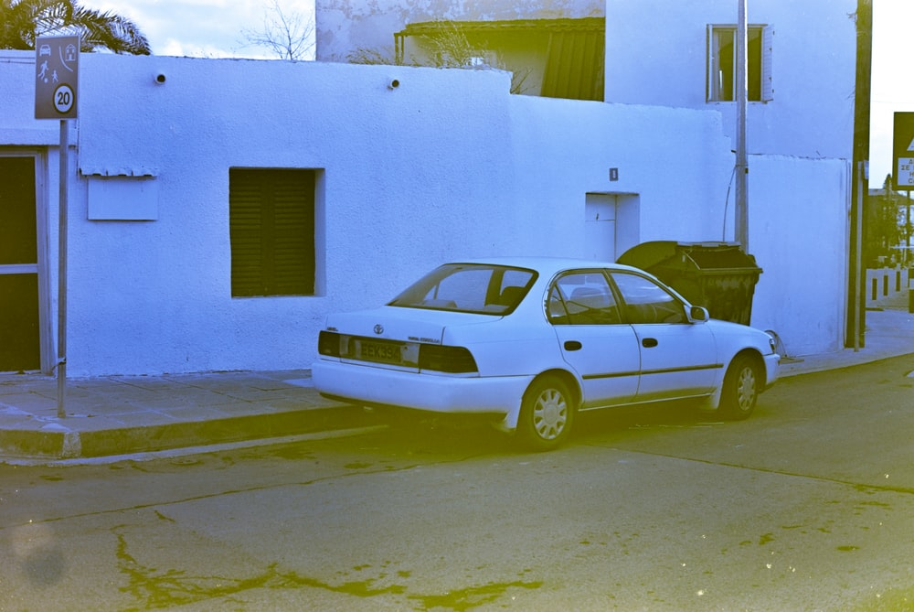 yellow sedan parked beside blue concrete building during daytime
