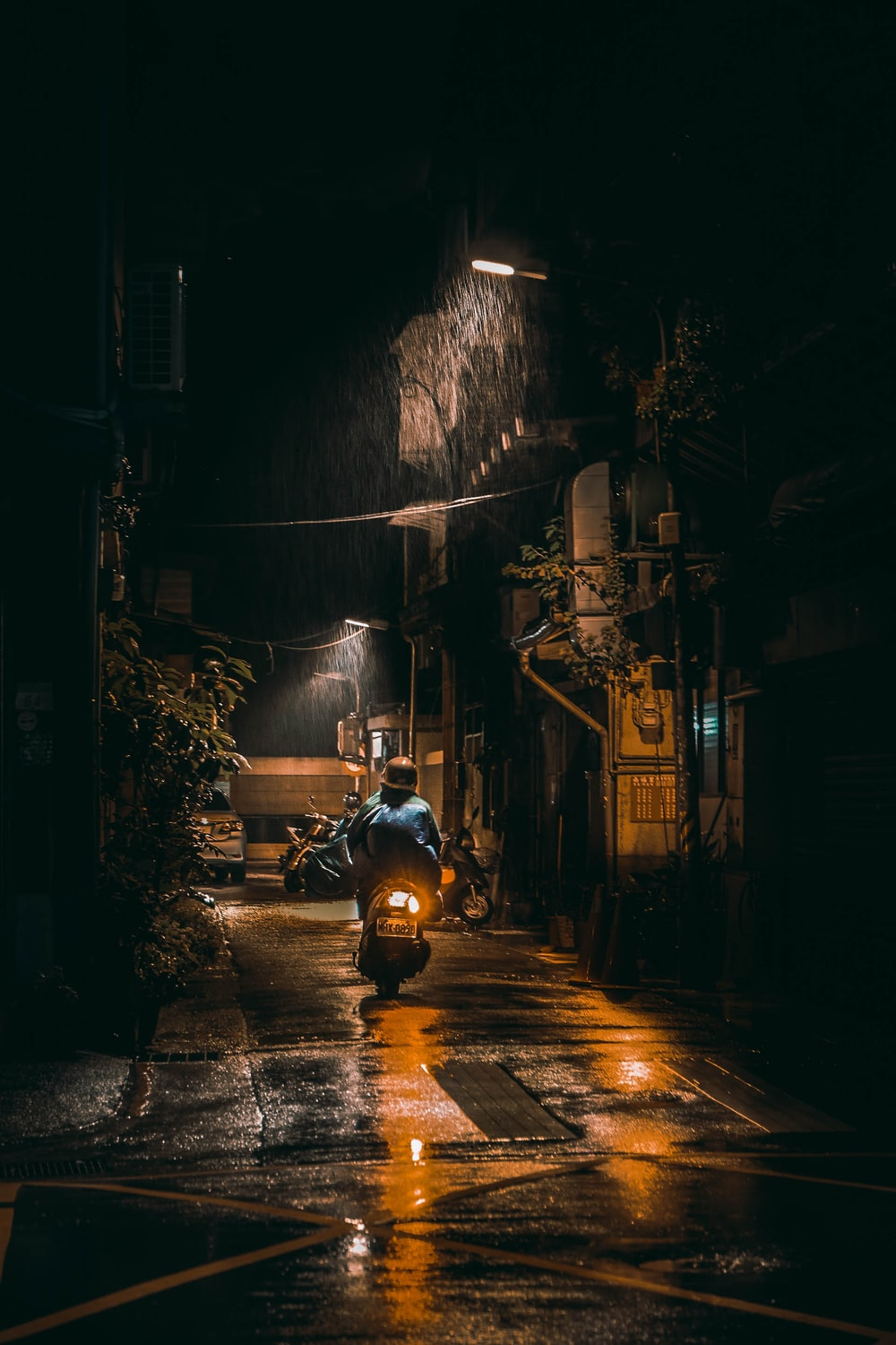 man in black jacket riding motorcycle on road during nighttime