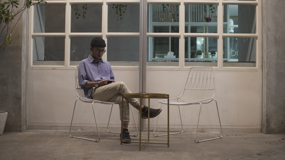 man in blue shirt sitting on white chair