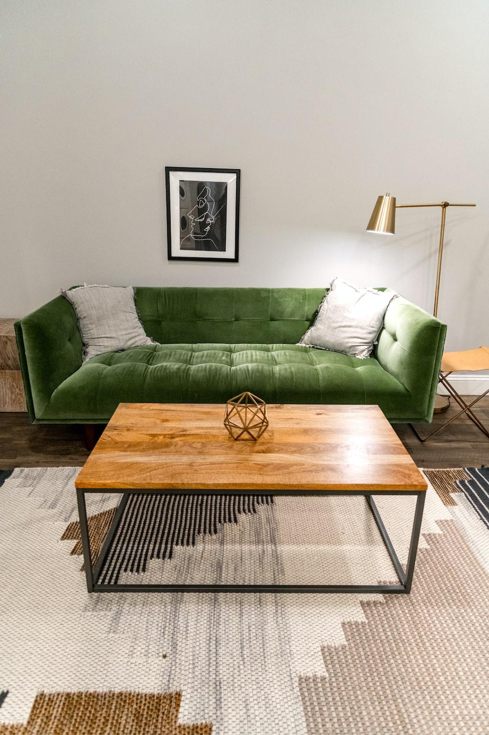 brown wooden table near green sofa