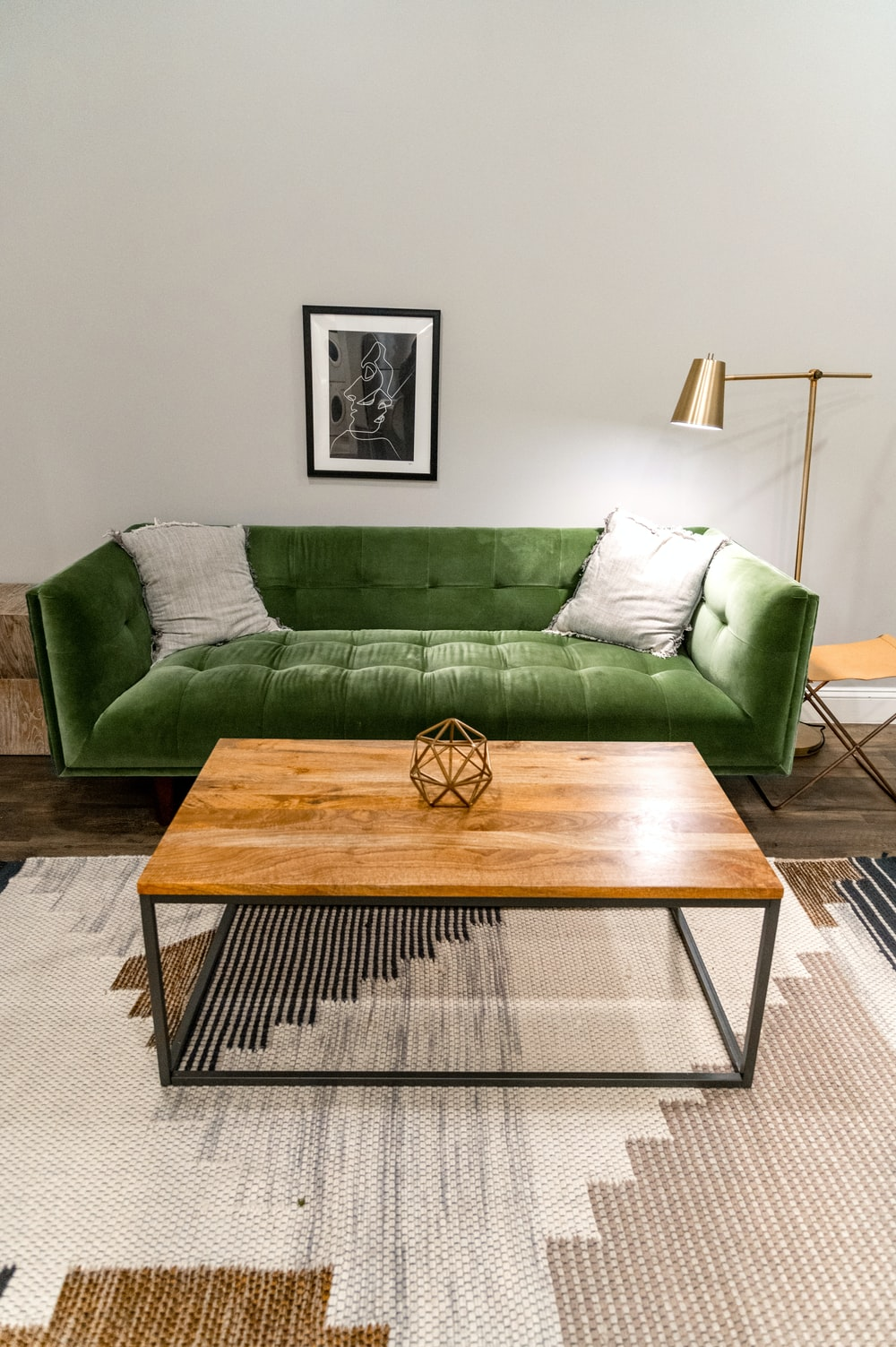 brown wooden table near green sofa