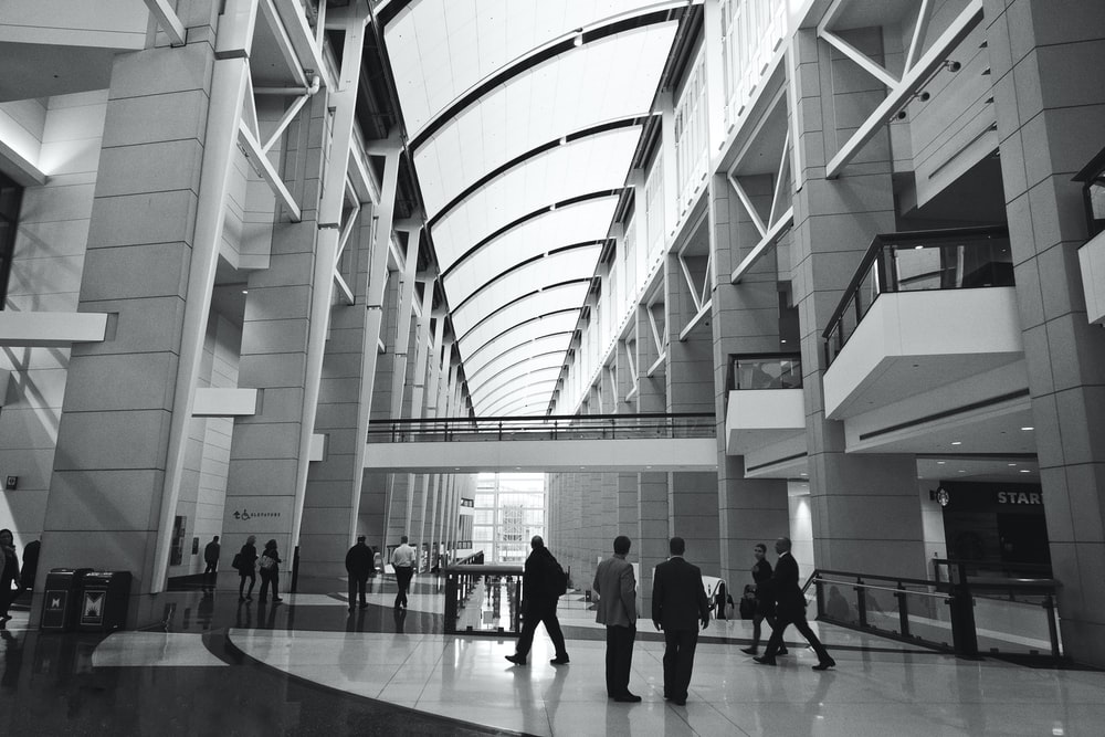 people walking inside building in grayscale photography