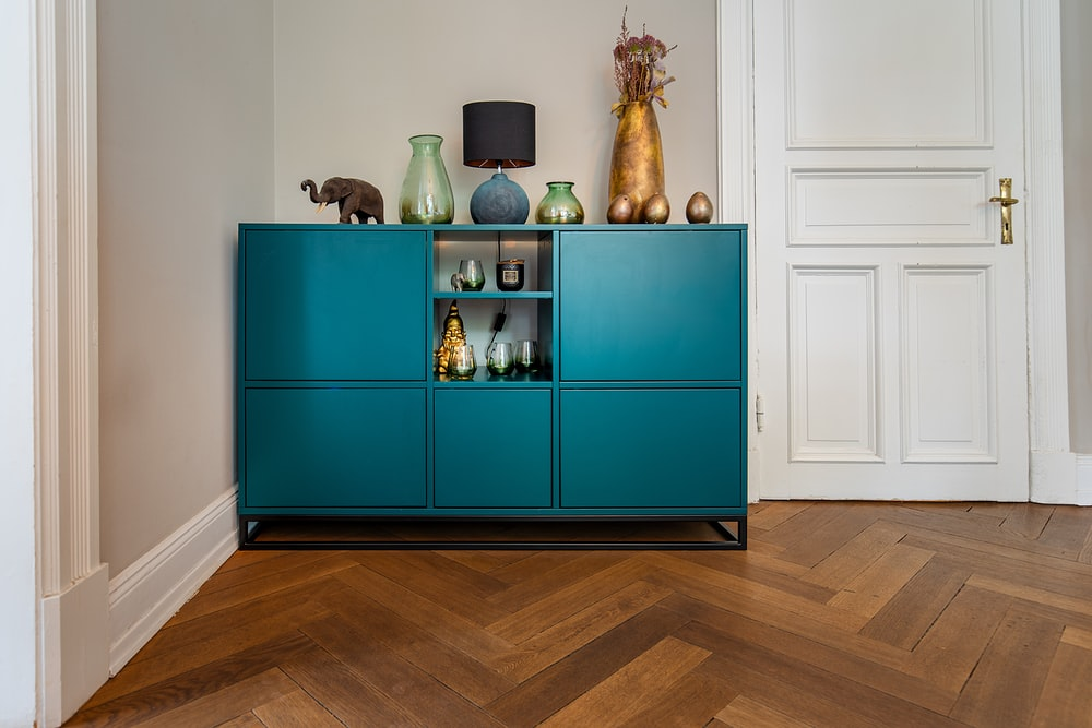 green wooden cabinet with figurines
