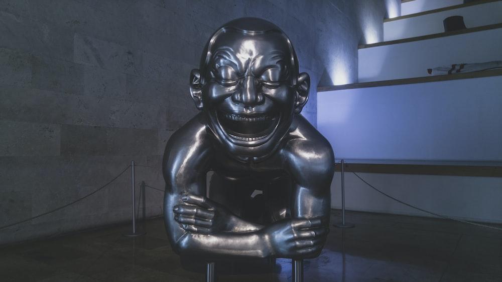 black human skull statue near blue wall
