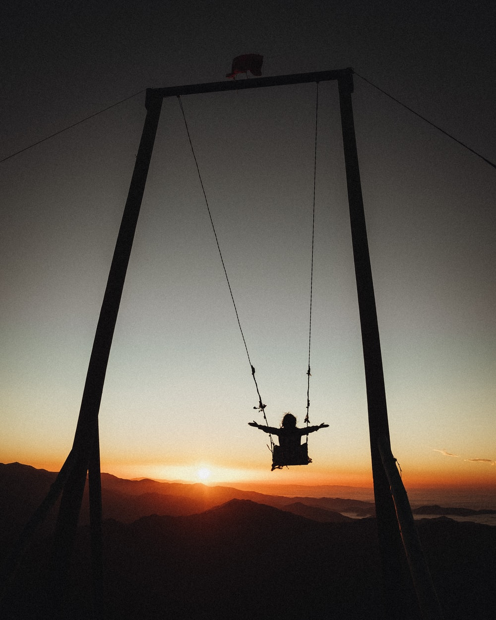 silhouette of person riding on swing during sunset
