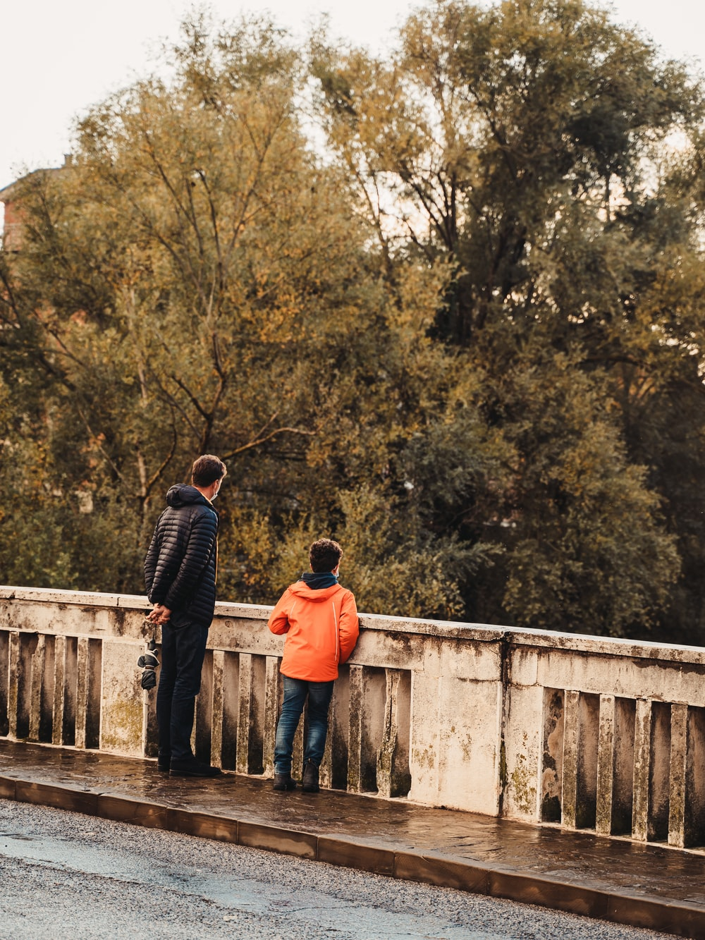 man and woman standing on wooden bridge during daytime