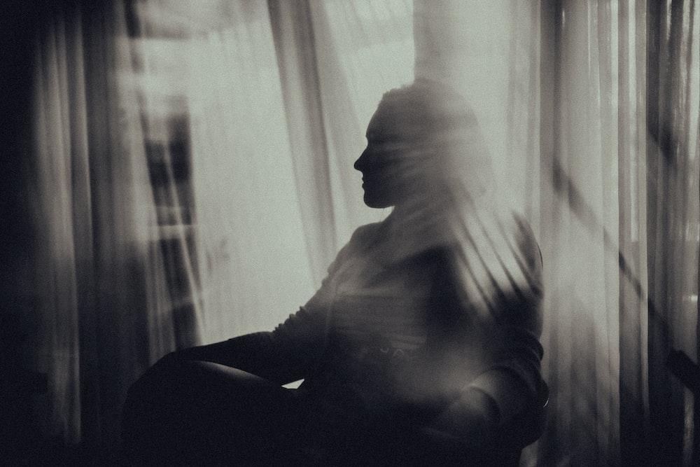 man sitting on chair near window