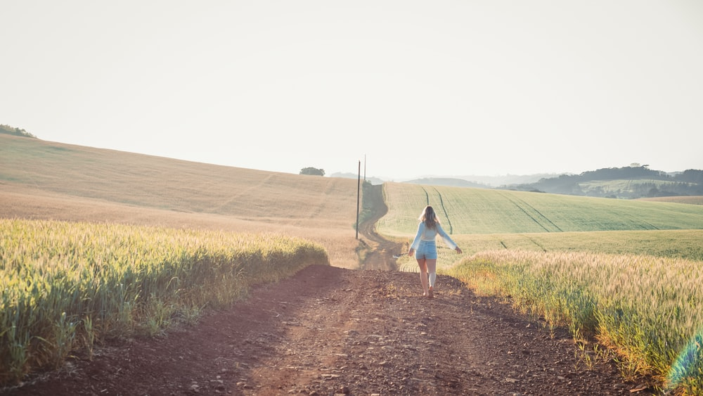 woman in white dress walking on dirt road between green grass field during daytime