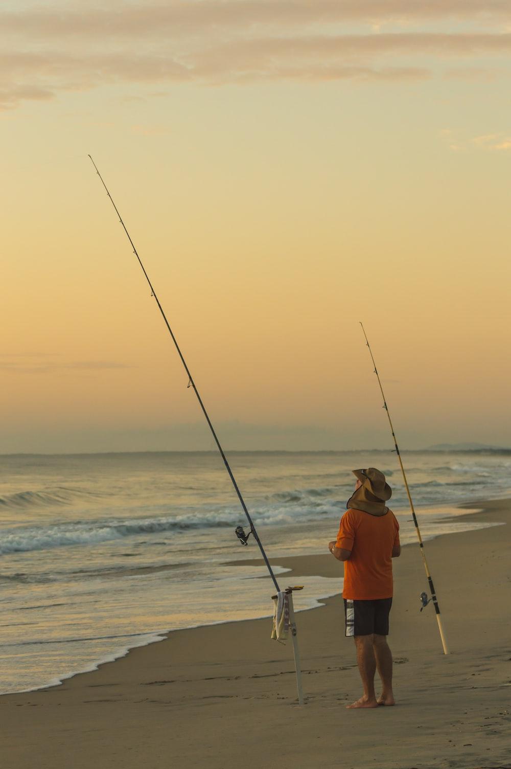 man in orange shirt fishing on sea during daytime